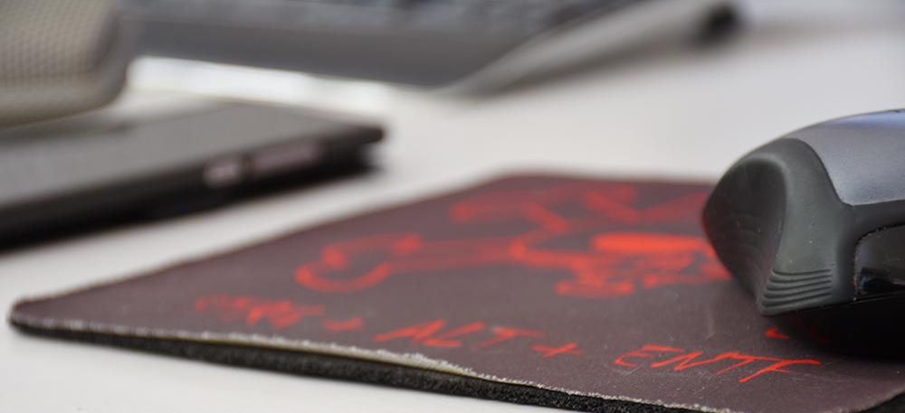 Online-Marketing mit Fleiß: Computermaus auf einem abgewetzten Mousepad mit Smartphone und Tatstatur im Hintergrund