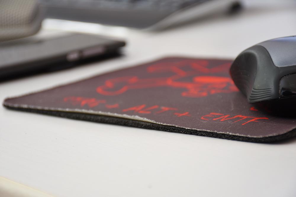 Computermaus auf einem abgewetzten Mousepad mit Smartphone und Tatstatur im Hintergrund